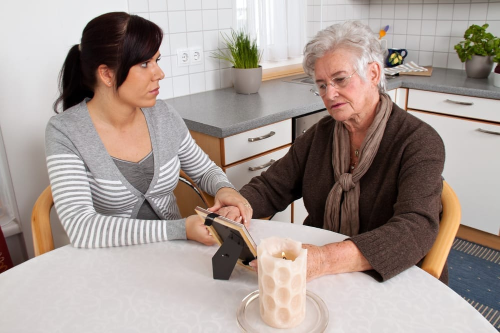 Two women looking at photo in kitchen