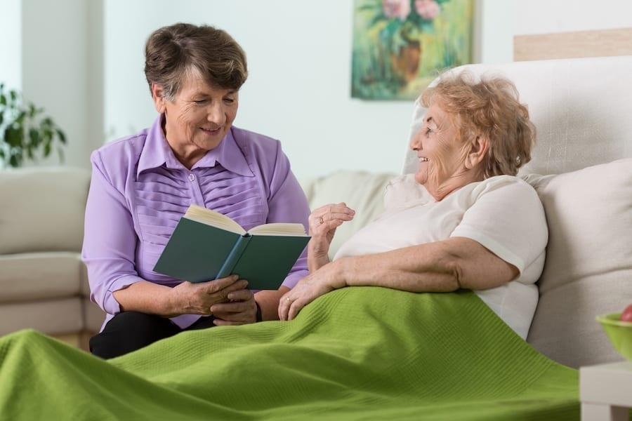 women talking at bedside smiling