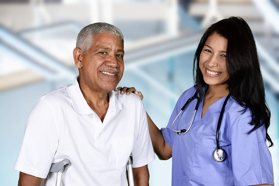 Female nurse holding male patient smiling