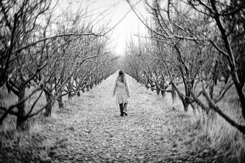 woman walking through winter trees