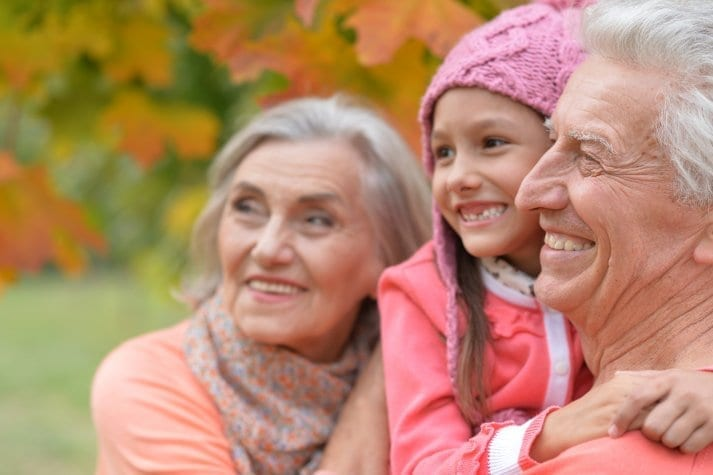grandparents and granddaughter smiling in fall
