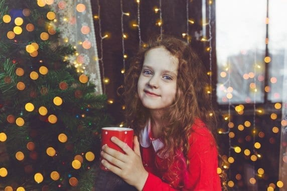 girl standing in front of christmas tree